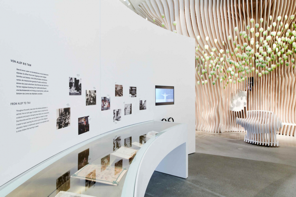 white room with showcase with exhibition objects and photos on the wall