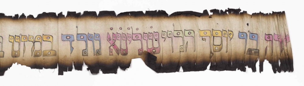 Burned strip of paper with colorful Hebrew letters
