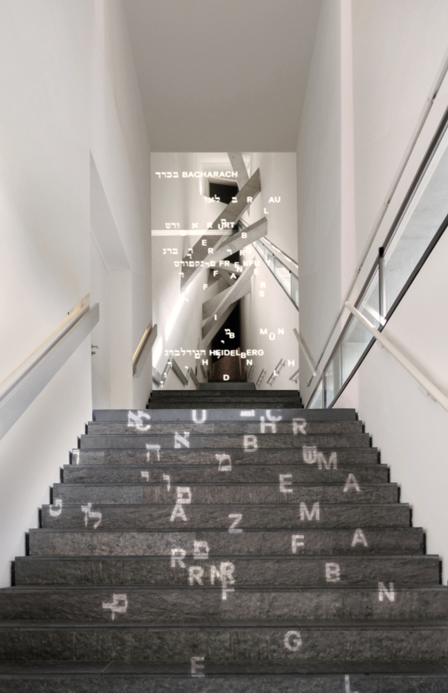 Lange Treppe mit projizierten hebräischen und lateinischen Buchstaben, die sich zu Städtenamen formen