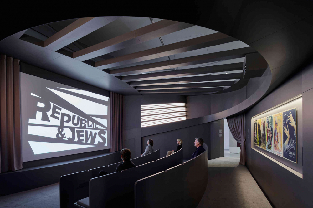 cinema hall with three rows and spectators, on the screen stands Republic & Jews