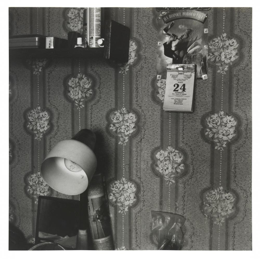 Eine Aufnahme der Künstlerin Rita Ostrovska zeigt eine Tapetenwand mit Kalender, im Vordergrund ist eine Stehlampe zu sehen