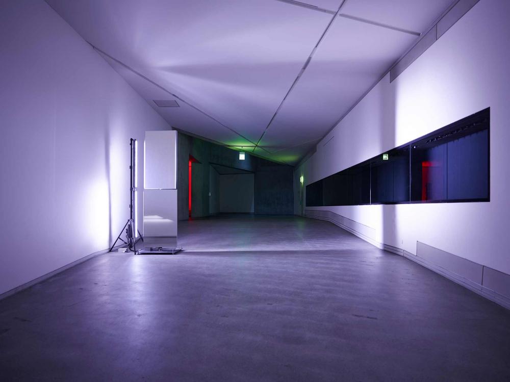 Eine Leuchte taucht den Raum in bläulich-violettes Licht