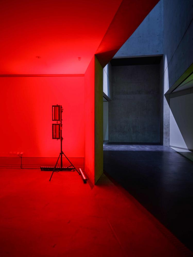 Links erleuchtet rotes Licht den Raum, rechts ist das Grau der Wände zu sehen