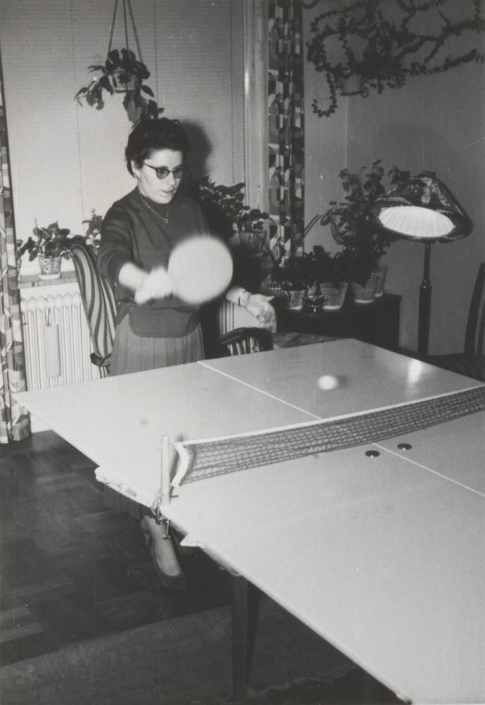 Eine Frau spielt Pingpong, im Hintergrund eine Stehlampe