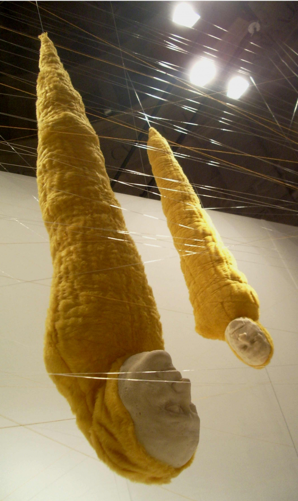 Two yellow chrysalis sculptures with human faces hanging upside down from the ceiling