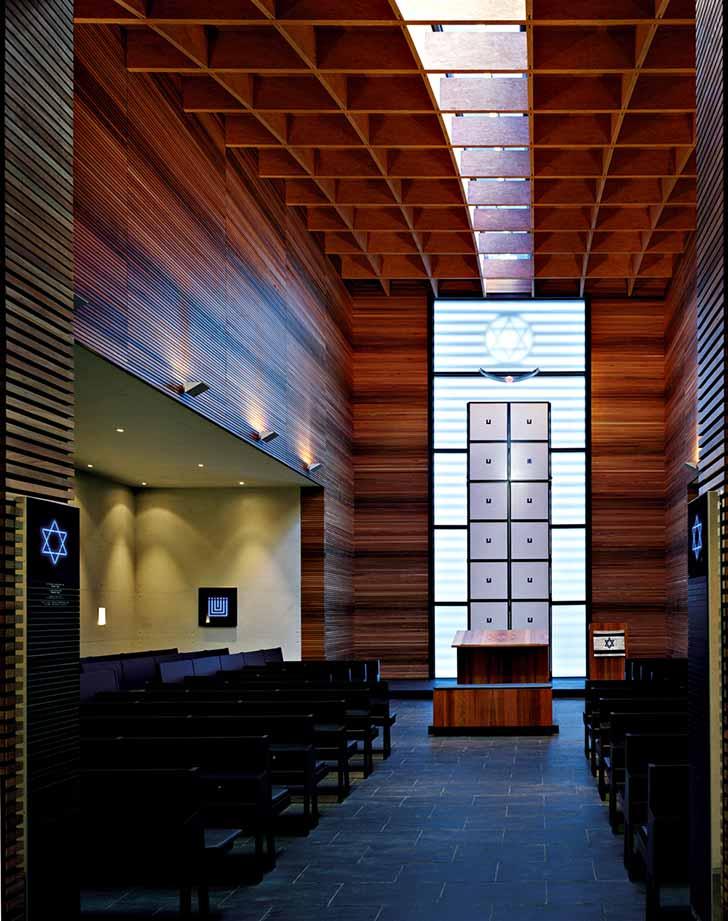 Innenaufnahme der Synagoge, holzverkleidete Wand, Toraschrein ist blau erleuchtet