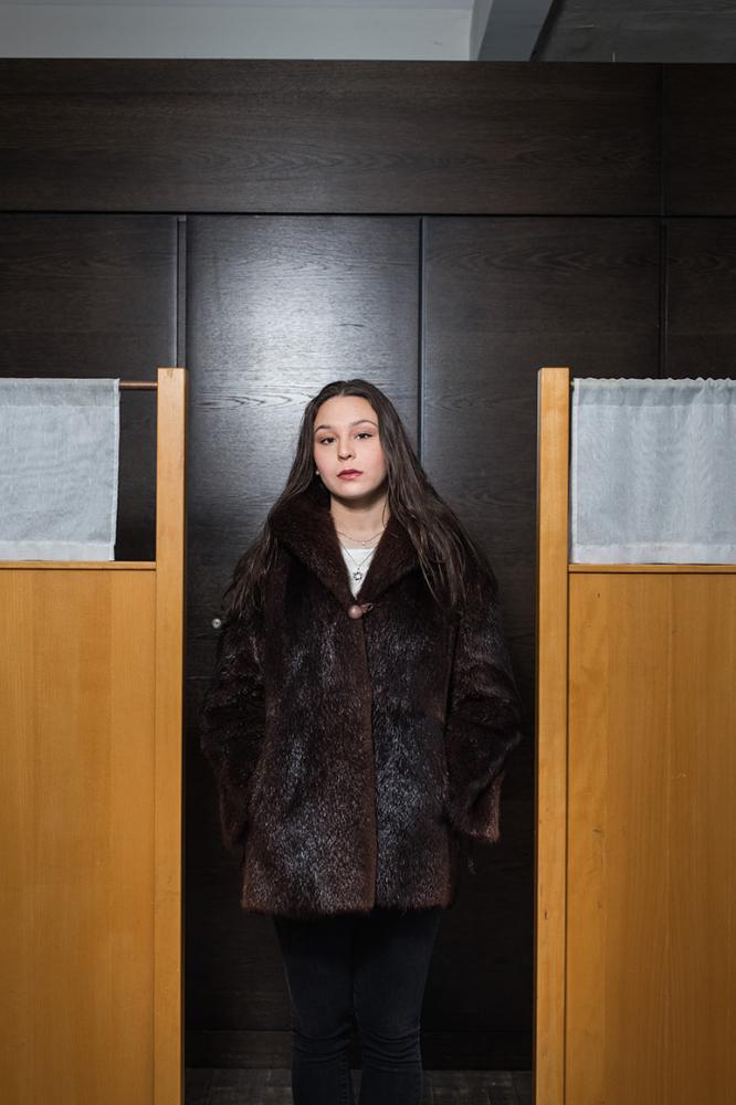 Photo: a woman in a fur coat in front of a dark veneer panel