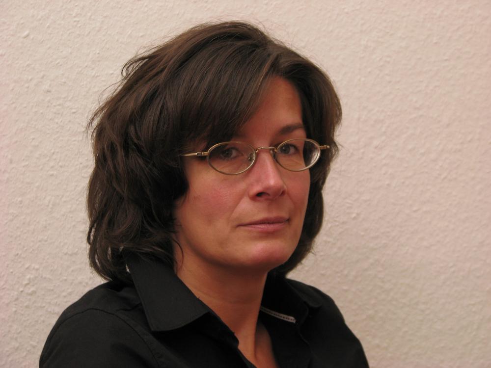 Fotografisches Porträt von Karen Körber, sie hat dunkle Haare und trägt eine Brille mit ovalen Gläsern