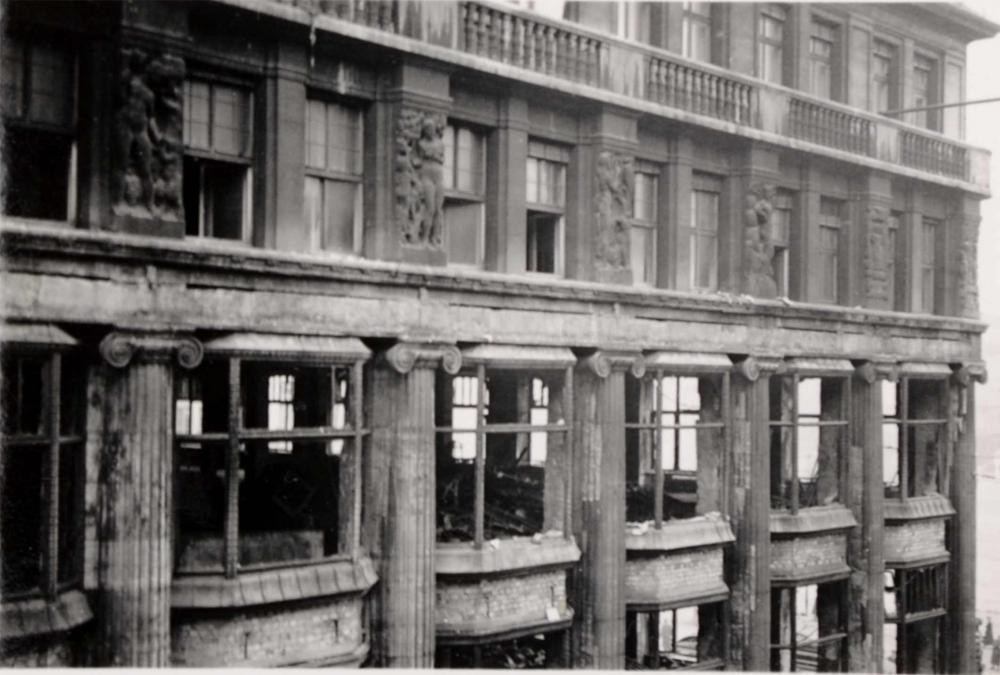 Das Foto zeigt ein Gebäude mit zerstörten Fensterscheiben und die Verwüstung im Inneren der ersten beiden Stockwerke des Kaufhauses. Das Foto ist auf Höhe des 2. Stockwerks, vermutlich vom gegenüberliegenden Gebäude aus, aufgenommen worden.