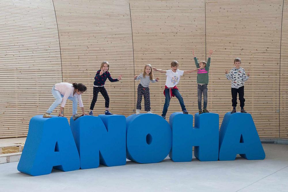 Kinder turnen auf lebensgroßen Buchstaben, die den Schriftzug ANOHA bilden