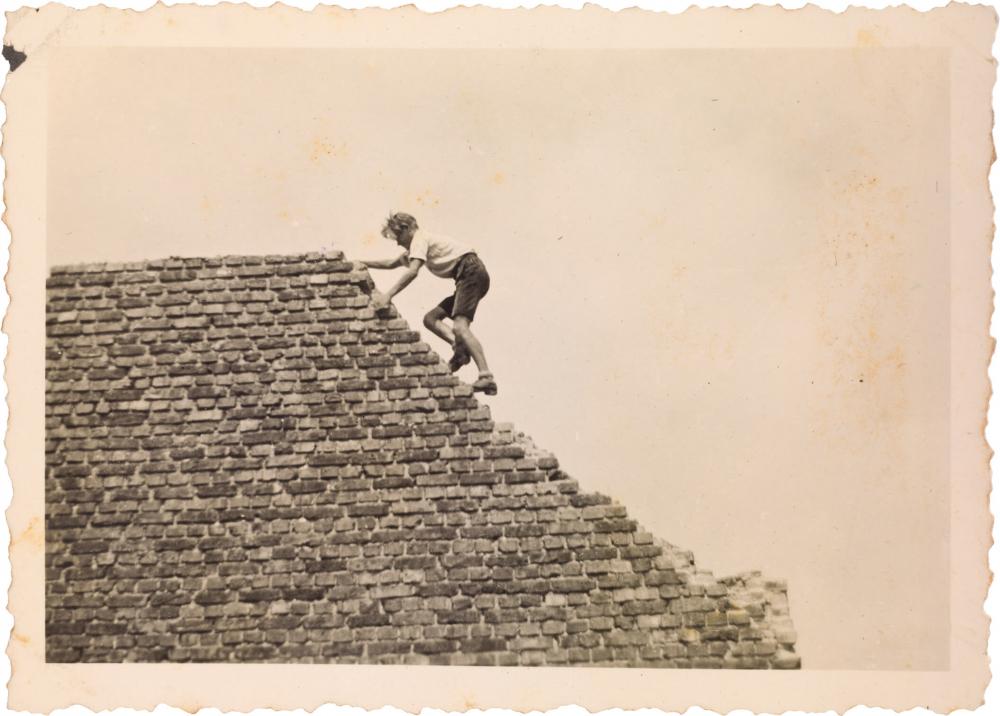 Schwarz-Weiß-Foto eines jungen Mannes in kurzen Hosen und weißem Hemd, der waghalsig eine Brandmauer erklimmt