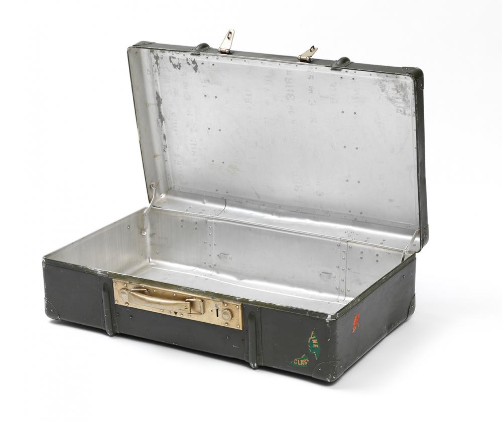 Geöffneter olivfarbener Metallkoffer mit Aufklebern und goldfarbenen Beschlägen
