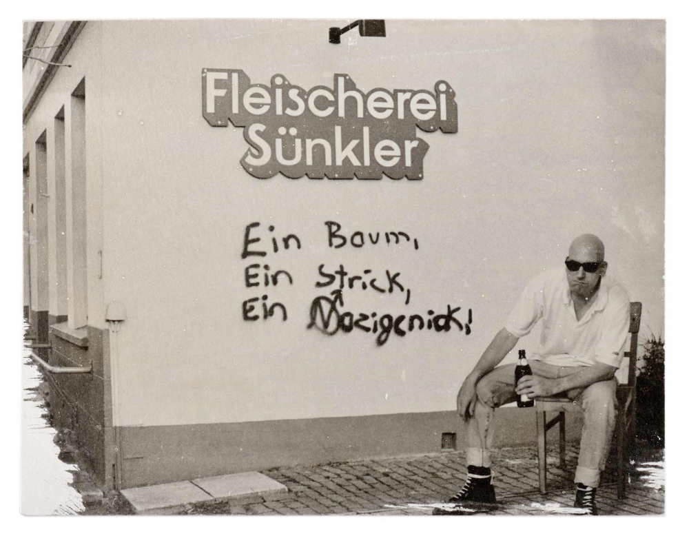 A man wearing sunglasses and holding a beer sits next to a wall with graffiti