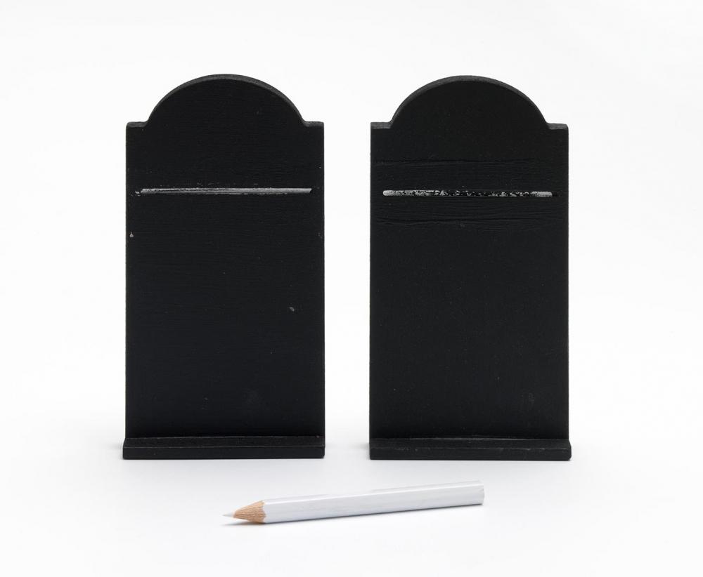 Zwei »Gebotstafeln« mit geschwungener Oberkante aus einer mitteldichten Holzfaserplatte mit schwarzer Tafelfarbe lackiert, davor liegt ein weißer Kreidestift