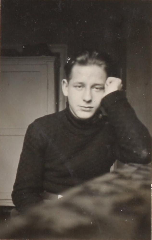 Schwarz-Weiß-Porträtfoto eines jungen Mannes, der direkt in die Kamera schaut. Er stützt den Ellbogen auf den Tisch auf, an dem er sitzt, seine Schläfe ist auf seiner linken, zur Faust geballten Hand aufgestützt