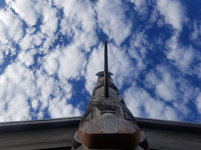 Photography of a totem pole in front of a cloudy sky