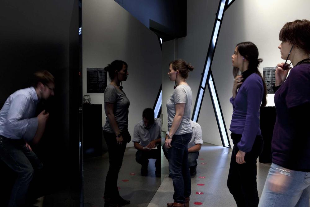 Mehrere Personen mit Kopfhörern vor einer der Skulpturen