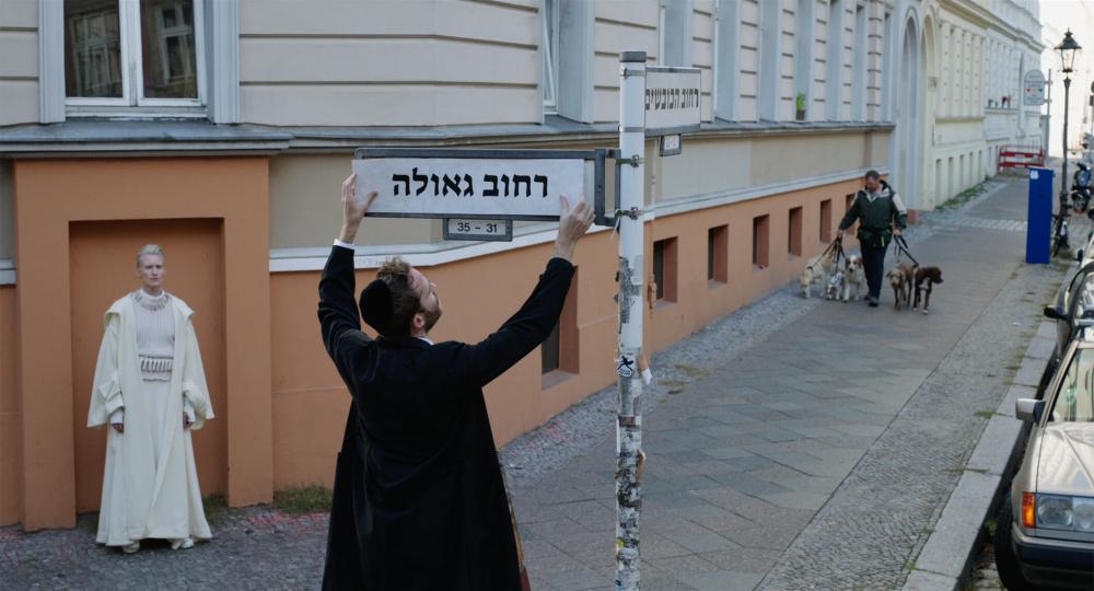 Ein Mann mit Kippa montiert ein Straßenschild mit hebräischem Straßennamen. Links von ihm steht eine Frau in weißen Gewändern im Rahmen einer zugemauerten Tür, die Teil des orangefarbigen Sockels eines renovierten Altbaus ist, und schaut ihm zu