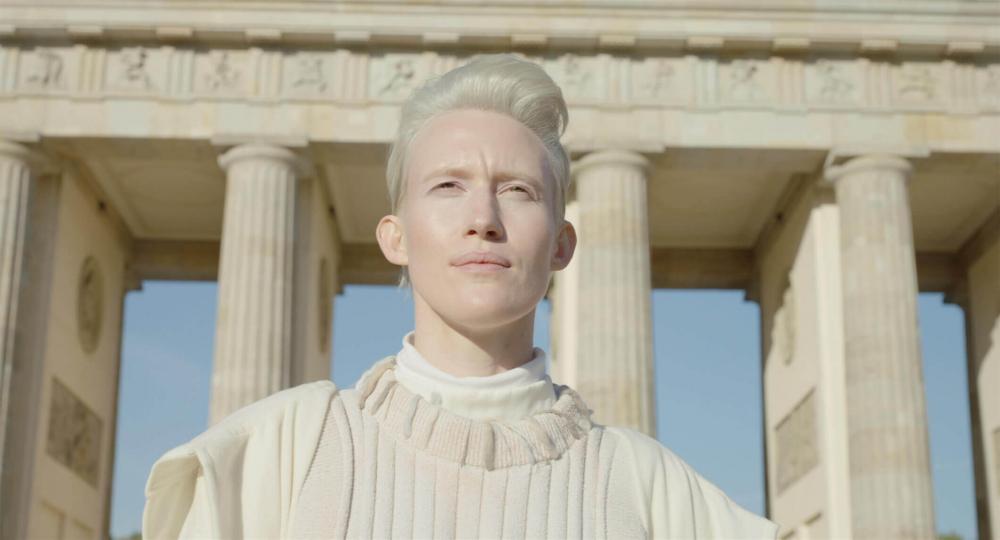 Brustbild einer androgyn wirkenden platinblonden Person mit kurzem Haar und weißem Oberteil. Hinter ihr sind die Säulen des Berliner Brandenburger Tors vor blauem Himmel zu sehen