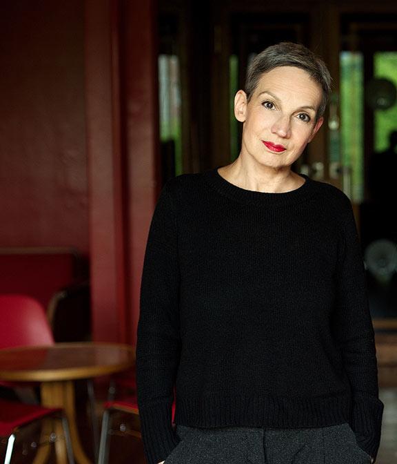 Porträtbild von Marion Brasch mit Händen in den Hosentaschen und Bartisch im Hintergrund
