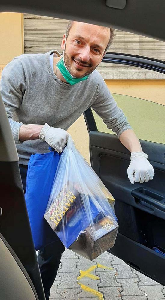 Blick vom Beifahrersitz auf einen Mann mit Tüte und Handschuhen, der an der Fahrertür ins Auto steigt