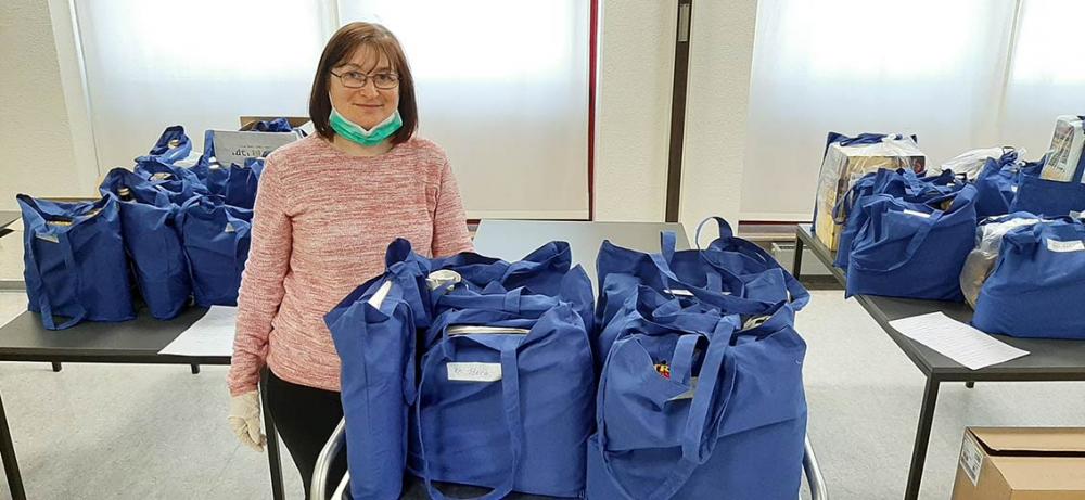 Eine Frau mit runtergeklapptem Mundschutz zwischen vielen gepackten Taschen