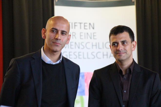 Porträtfoto von zwei Männern in Frontalansicht. Sie lächeln und tragen Anzüge, aber keine Krawatten.