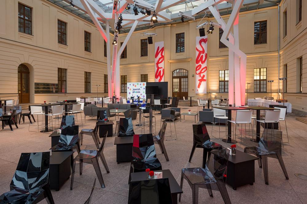 Stühle und kleine Tische im Glashof des Jüdischen Museums Berlin