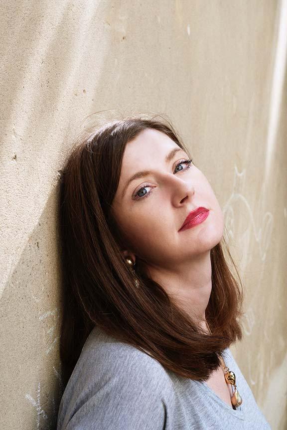 Frau mit langen braunen Haaren und rotem Lippenstift lehnt mit dem Kopf an einer Wand und schaut in die Kamera