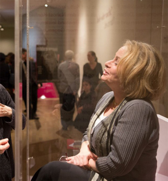 A woman behind glass, in the background visitors of the exhibition
