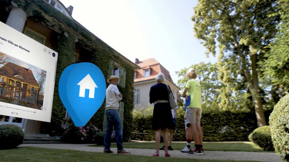 Fünf Menschen stehen vor einer Villa. Am linken Bildrand ist ein Browserfenster mit einem Foto und abgeschnittenen Text zu sehen – daneben ein blauer Pin mit einem weißen Haus-Symbol.