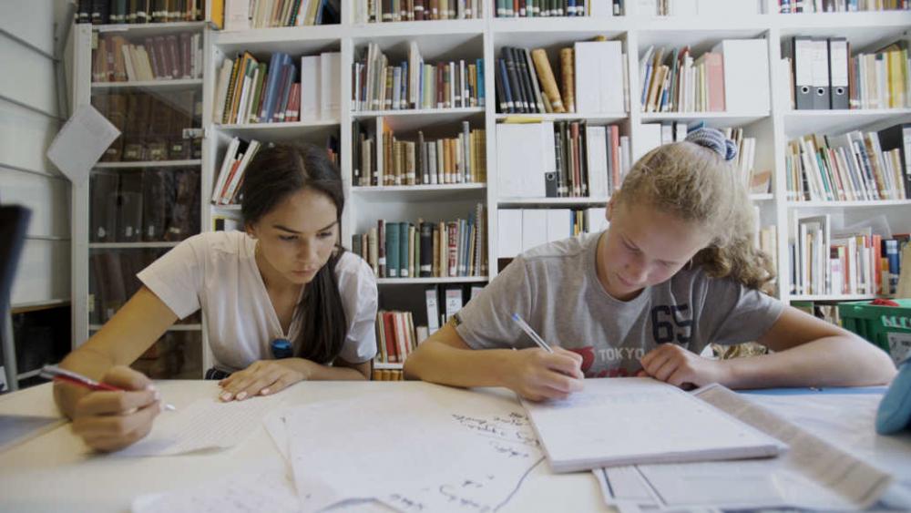 Zwei Jugendliche sitzen hinter einem Regal der Bibliothek des Steglitz Museums an einem Tisch und schreiben mit Stiften auf einem Notizblock.