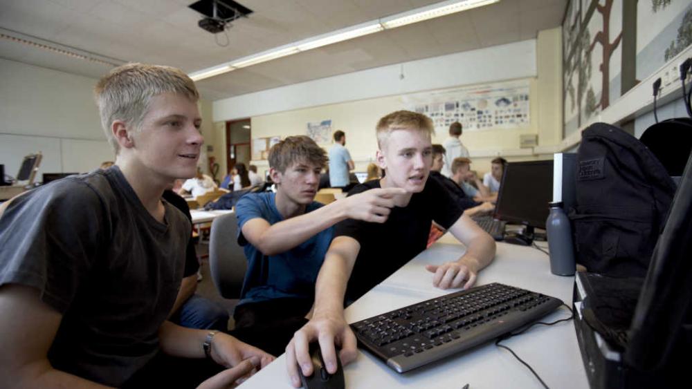 Jugendliche sitzen in einem großen Raum. Im Vordergrund sitzen drei Jugendliche an einer Tastatur.