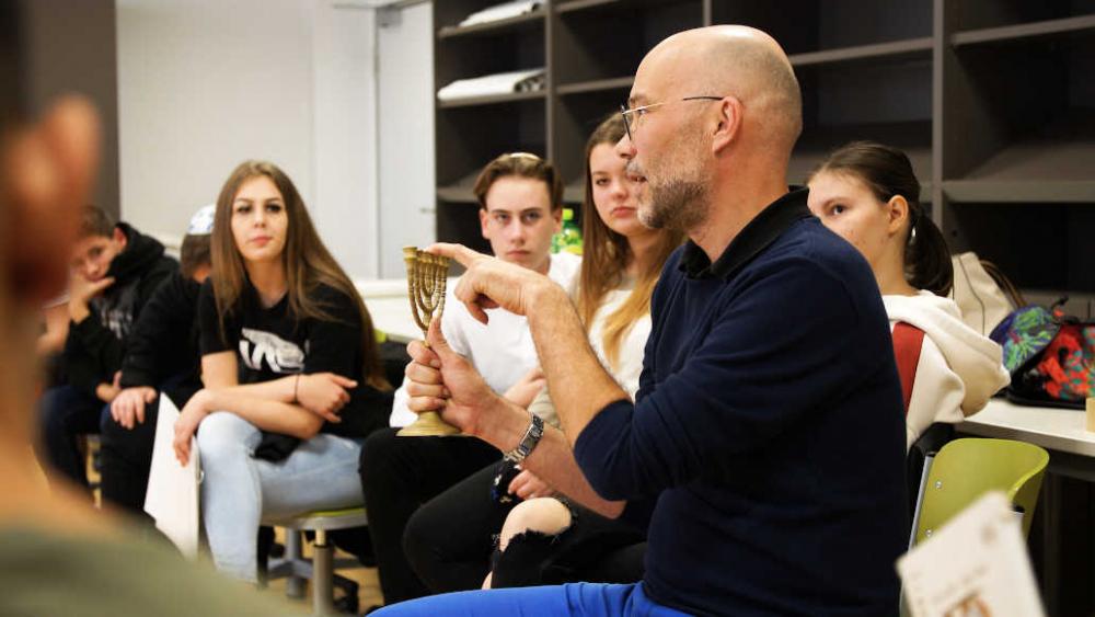 Ein Mann mit Brille hält einen Chanukkaleuchter in der Hand und redet. Um ihn herum sitzen Jugendliche.
