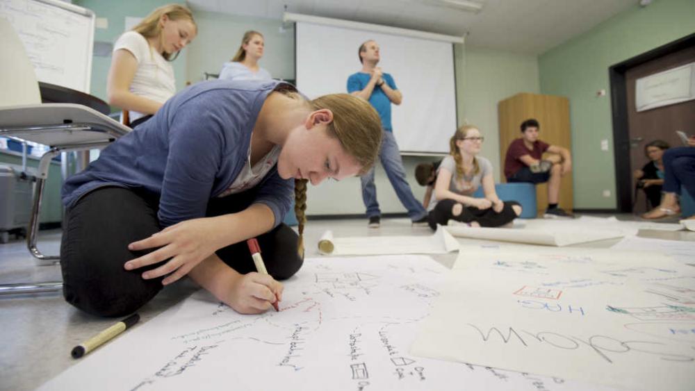In einem Raum mit einer Leinwand und einer Tafel sind Jugendliche und ein Erwachsener zu sehen. Auf dem Boden sind beschriftete Plakate verteilt. Im Vordergrund sitzt ein Mädchen auf dem Boden, die auf einem Plakat schreibt.