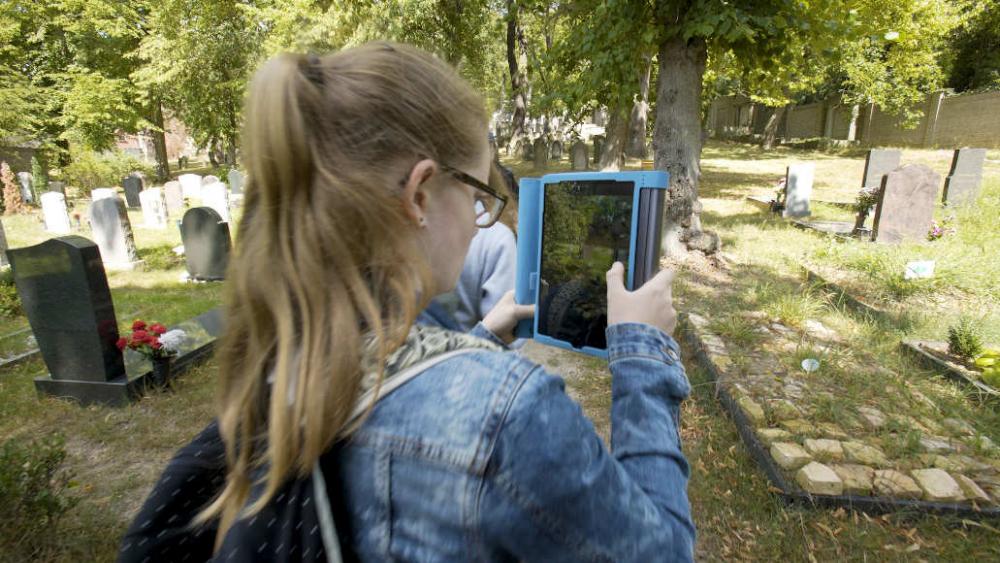 Ein Mädchen fotografiert mit einem Tablet einen Grabstein auf einem Friedhof.