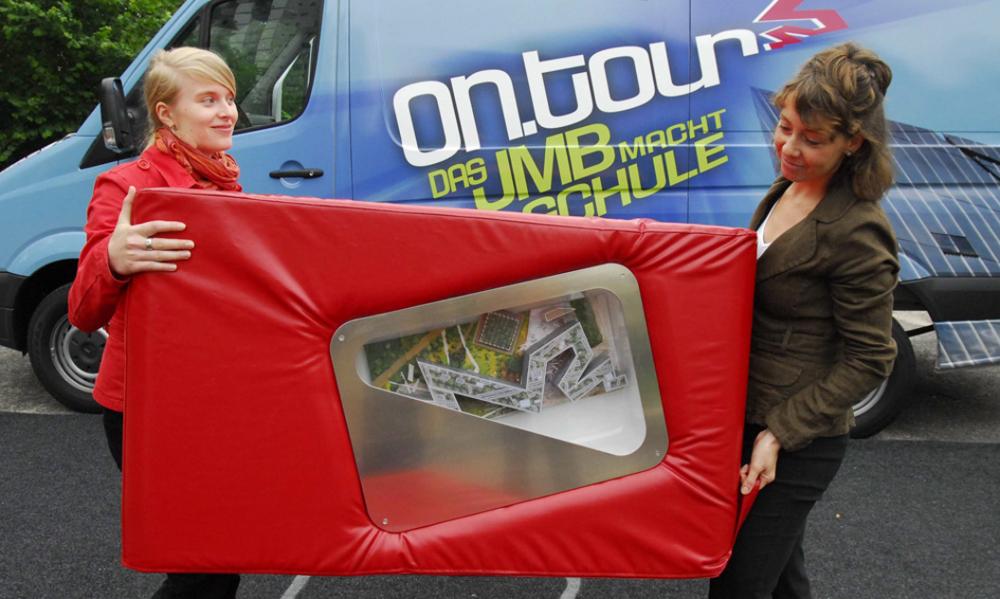 Zwei Mitarbeiterinnen von ontour tragen einen roten Sitzwürfel, in dem ein Modell des Libeskind-Baus vom Jüdischen Museumzu s