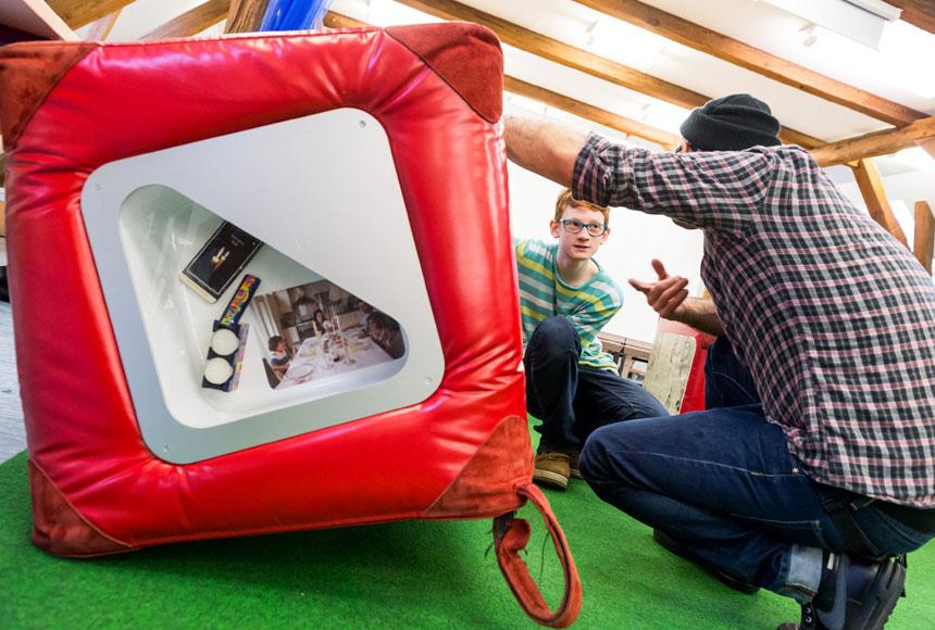 Einer der Guides hockt zusammen mit einem Schüler neben einem großen roten Würfel, in dem Ausstellungsstücke zu sehen sind.