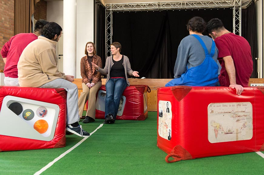 Jugendliche sitzen auf einigen Ausstellungswürfeln