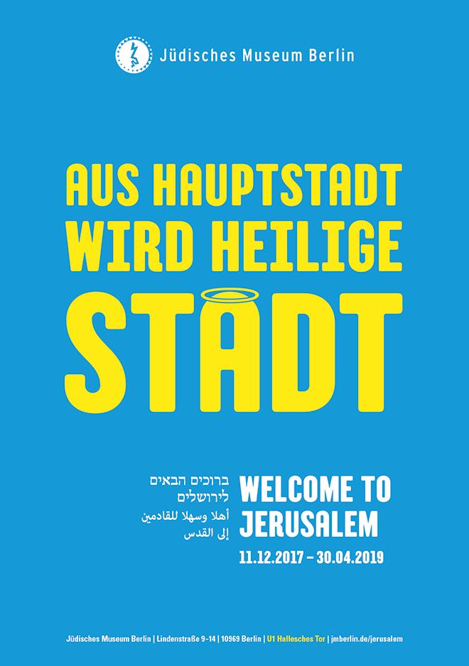 """Plakat mit der Aufschrift """"Aus Hauptstadt wird heilige Stadt"""", wobei das letzte a einen Heiligenschein trägt"""