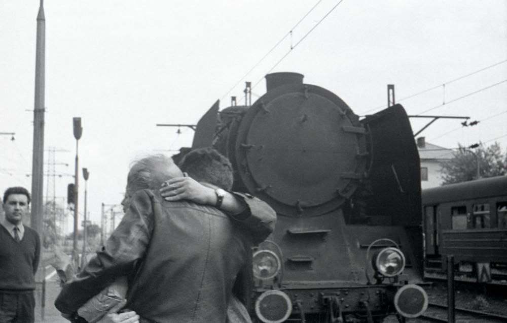 Two men hug at a train station