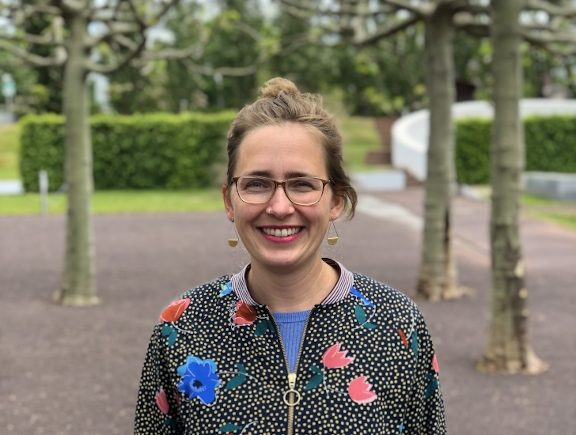 Porträt von Lisa Albrecht mit Brille und Jacke mit Blumenmuster im Museumsgarten