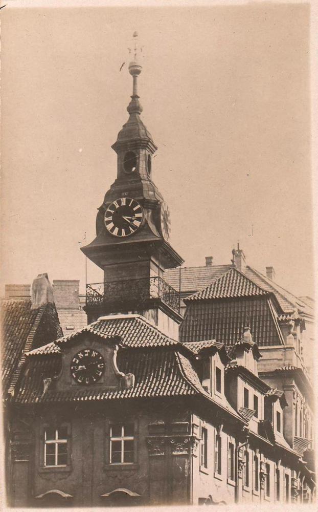 Schwarz-Weiß-Fotografie eines Hauses mit Türmchen und einer Uhr mit hebräischen Ziffern
