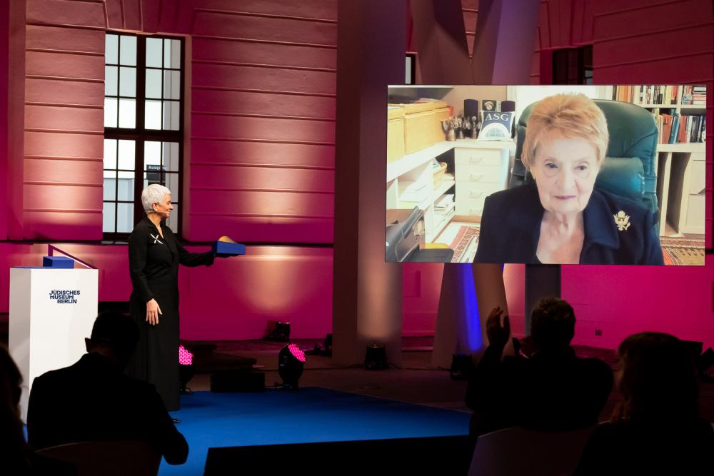 Hetty Berg steht auf einer Bühne, Madeleine Albright ist auf einer Leinwand per Video-Call zugeschaltet
