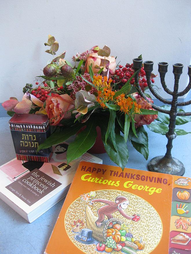 """Eine Menora, ein Blumenstrauß und das Buch """"Curious George"""""""