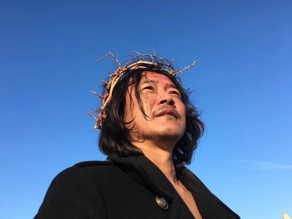 Porträtfoto eines Mannes mit Dornenkrone, von unten fotografiert, vor strahlend blauem Himmel