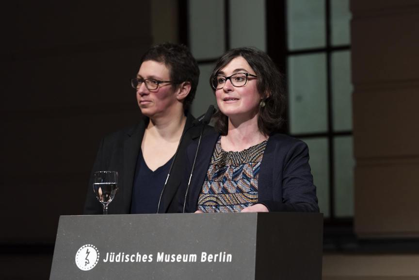 Alina Gromova steht an einem Pult auf dem das Logo und der Schriftzug des Jüdischen Museums stehen. Auf dem Pult steht ein Wasserglas. Hinter ihr steht Susan Kamel.