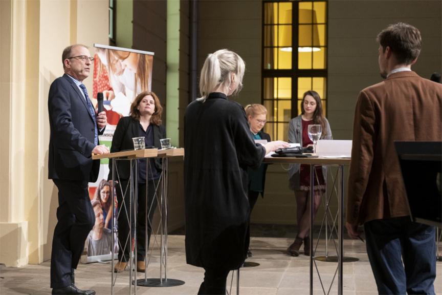 Markus Walz spricht. In seiner Hand ein Mikrophon. Hinter ihm steht Léontine Meijer-van Mensch.