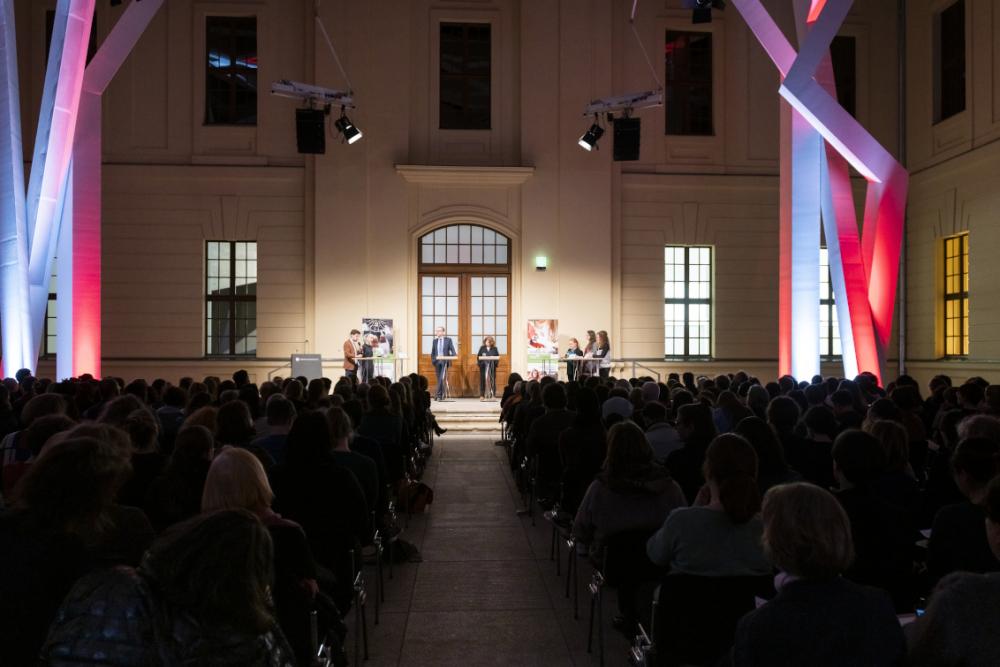 Im Glashof im Jüdischen Museum Berlin sind die Zuschauerränge gefüllt. Erhöht stehen Menschen an Pulten. Die Balken sind bunt beleuchtet.