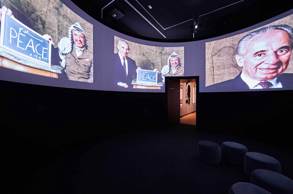 """Room with a cinema screen showing Shimon Peres and Yasser Arafat with a sign that reads """"peace."""""""